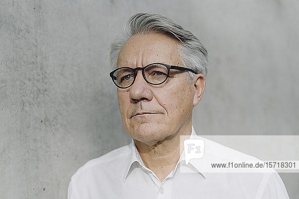 Porträt eines nachdenklichen Senior-Geschäftsmannes an einer Betonwand