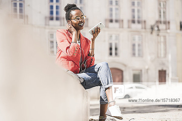 Lächelnde junge Frau mit Kopfhörern und Smartphone in der Stadt  Lissabon  Portugal