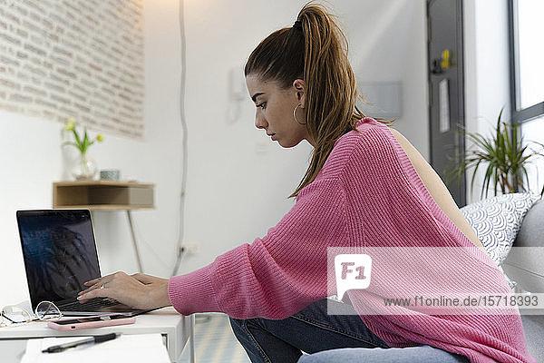 Junge Frau sitzt auf der Couch und arbeitet am Laptop