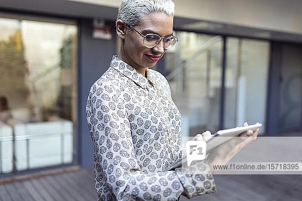 Selbstbewusste Geschäftsfrau benutzt Tablet im Freien