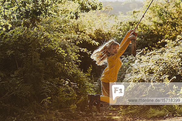 Glückliches kleines Mädchen schwingt auf einer Seilschaukel in der Natur
