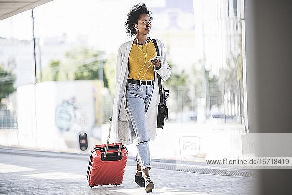 Junge Frau mit Handy und Kopfhörern am Bahnhof