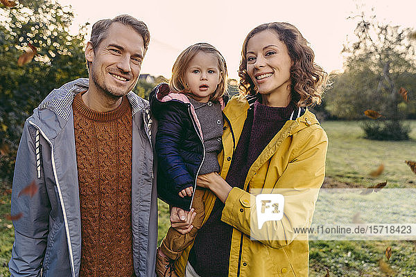 Porträt einer glücklichen Familie mit Tochter im Herbst im Freien