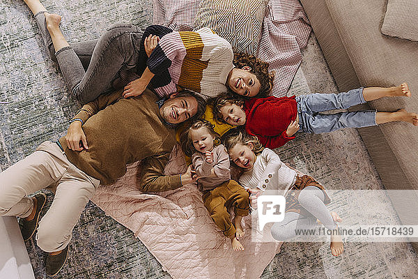 Happy family with three daughters lying on blankets at home