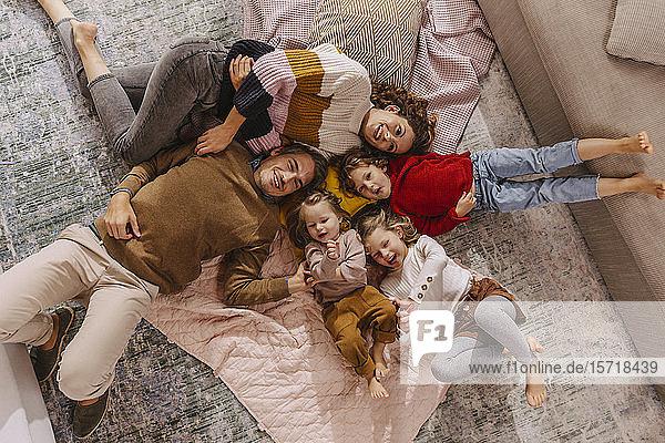 Glückliche Familie mit drei Töchtern  die zu Hause auf Decken liegen