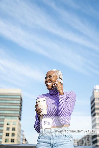 Porträt einer weißhaarigen Frau mit Smartphone und Kaffee zum Mitnehmen