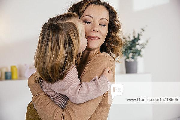 Mutter umarmt mit kleiner Tochter zu Hause