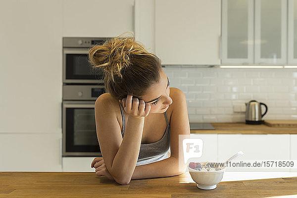 Weiblicher Teenager beim Frühstück in der Küche  seitwärts blickend