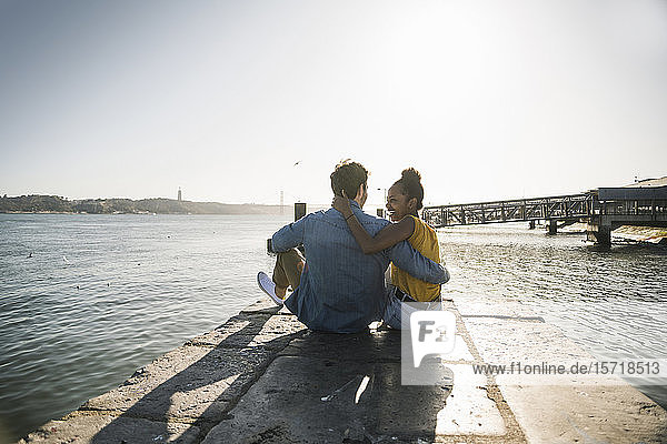 Rear view of young couple sitting on pier at the waterfront  Lisbon  Portugal