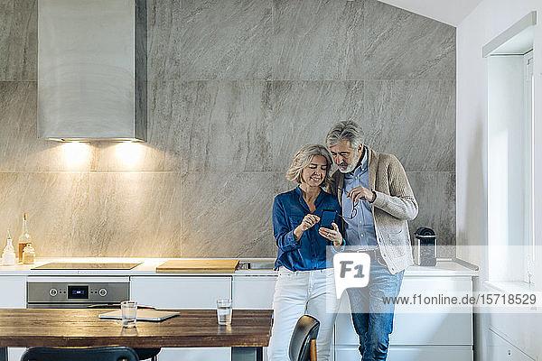 Ein erwachsenes Paar  das zu Hause in der Küche gemeinsam ein Mobiltelefon benutzt Ein erwachsenes Paar, das zu Hause in der Küche gemeinsam ein Mobiltelefon benutzt