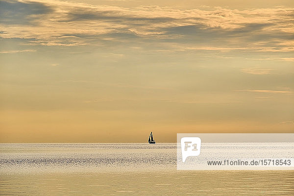 Italien  Trentino  Nago-Torbole  Silhouette eines Segelboots  das im launischen Morgengrauen über den Gardasee fährt