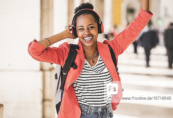Portrait of happy young woman with headphones listening to music in the city  Lisbon  Portugal