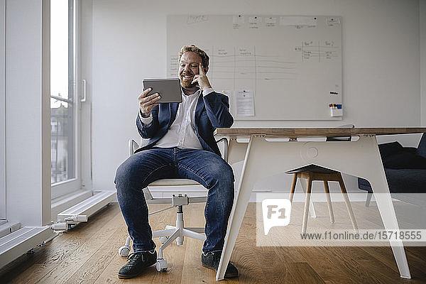 Lächelnder Geschäftsmann mit Tablett im Büro
