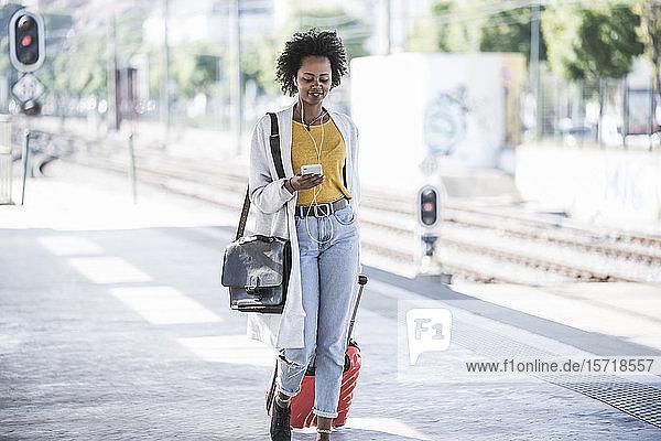Lächelnde junge Frau mit Handy und Kopfhörern am Bahnhof