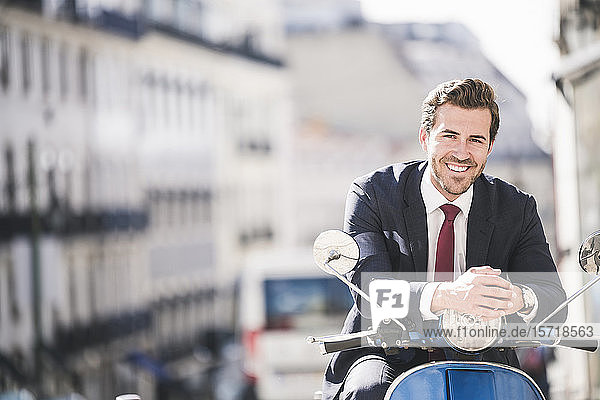 Portrait of smiling young businessman on motor scooter in the city  Lisbon  Portugal