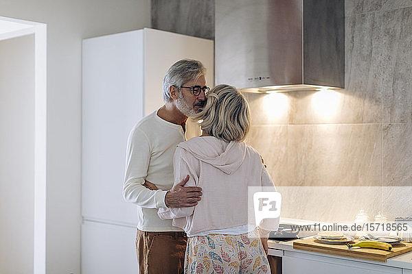 Liebevolles reifes Paar in der häuslichen Küche Liebevolles reifes Paar in der häuslichen Küche
