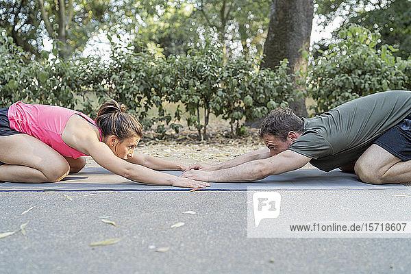 Mann und Frau  die sich im Freien auf einer Gymnastikmatte ausstrecken Mann und Frau, die sich im Freien auf einer Gymnastikmatte ausstrecken