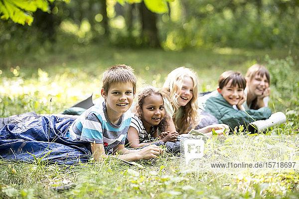 Schulkinder  die im Wald zelten und in Schlafsäcken liegen