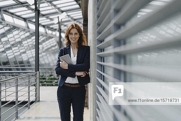 Porträt einer lächelnden Geschäftsfrau  die in einem modernen Bürogebäude ein Tablett hält