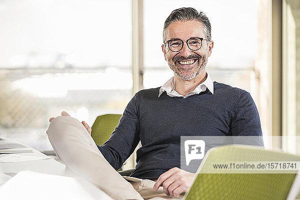 Porträt eines lächelnden reifen Geschäftsmannes  der im Büro am Schreibtisch sitzt
