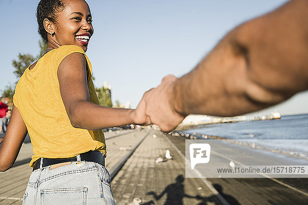Happy young woman holding hand of her boyfriend on pier at the waterfront  Lisbon  Portugal