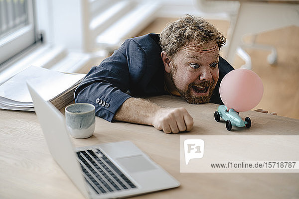 Businessman playing with miniature toy car on desk in office