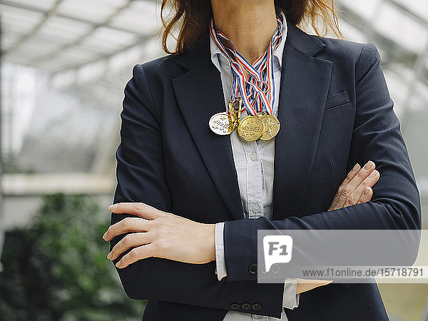 Nahaufnahme einer Geschäftsfrau  die im Amt Medaillen um den Hals trägt