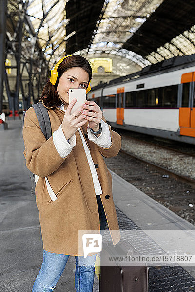 Young woman with headphones and cell phone at the train station