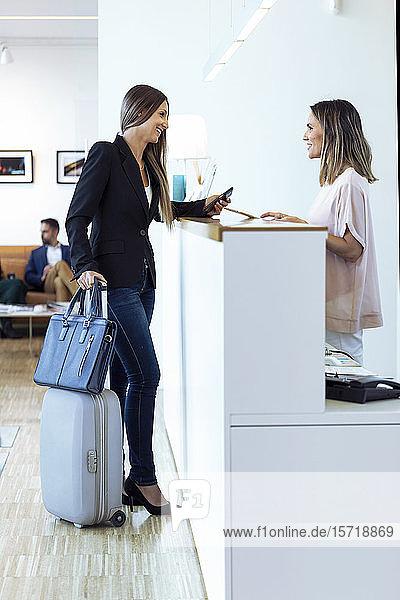 Lächelnde Geschäftsfrauen im Gespräch mit Frau am Empfang