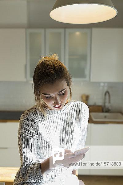 Junge Frau benutzt Smartphone zu Hause