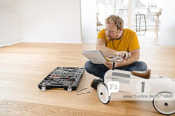 Man assembling toy car reading instructions