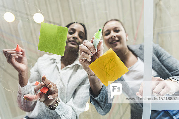 Two young businesswomen working on adhesive notes on glass table