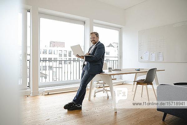Lächelnder Geschäftsmann mit Laptop im Büro