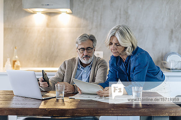 Mature couple with papers and laptop on kitchen table at home