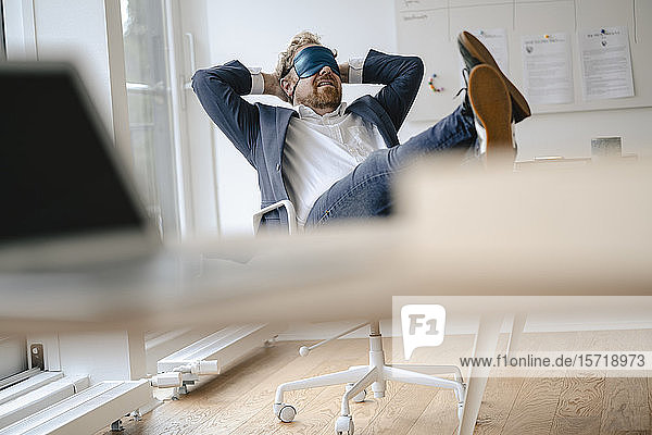 Businessman having a power nap at desk in office