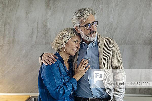 Liebevolles  reifes Paar  das sich zu Hause umarmt Liebevolles, reifes Paar, das sich zu Hause umarmt