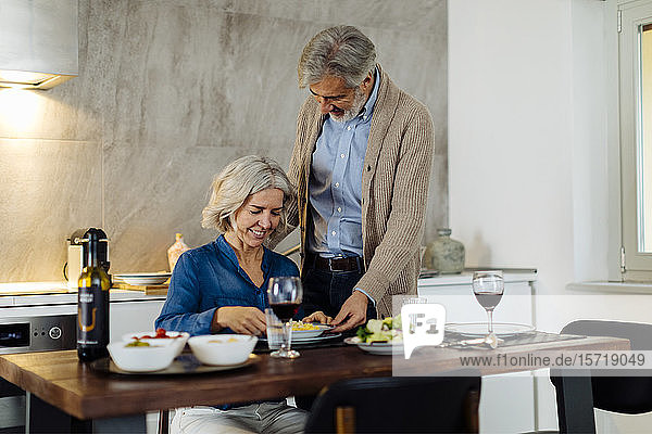 Mature man serving dinner to his wife in kitchen at home