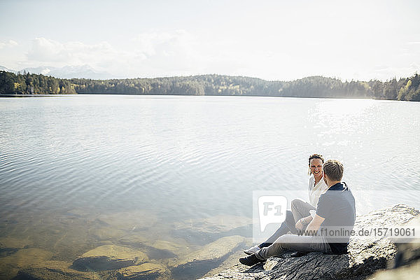 Happy couple sitting at the lakeside  Forstsee  Carinthia  Austria