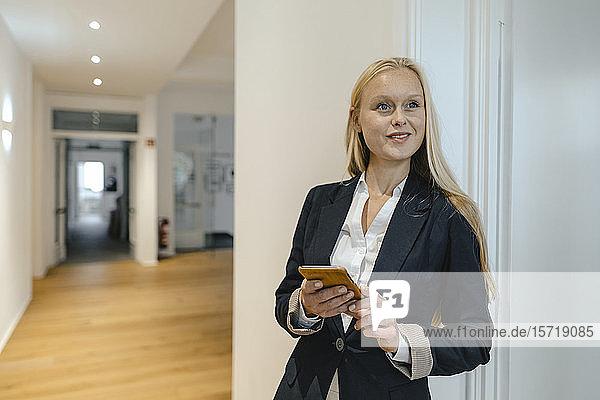 Lächelnde junge Geschäftsfrau mit Handy im Büro