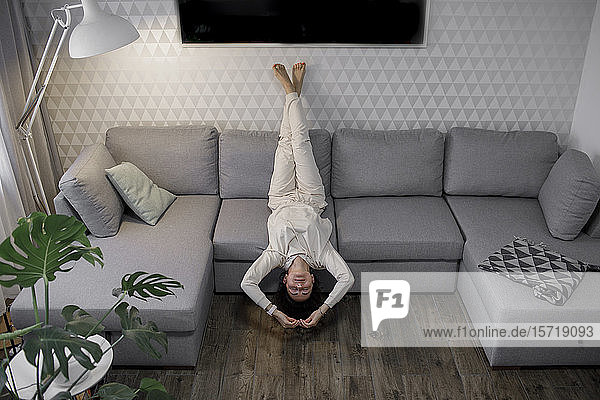 Frau entspannt kopfüber auf der Couch