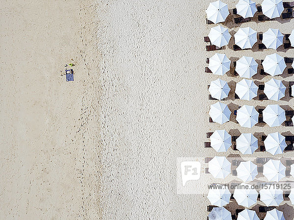 Indonesia  Bali  Aerial view of man sunbathing in front of rows of beach umbrellas on sandy coastal beach of Nusa Dua