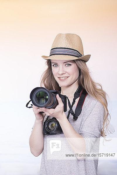 Porträt einer lächelnden jungen Frau beim Vergleich zweier verschiedener Kameras