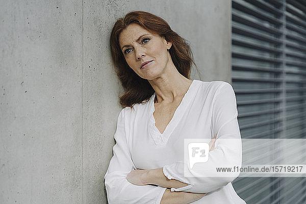 Porträt einer nachdenklichen Geschäftsfrau  die gegen eine Betonwand lehnt