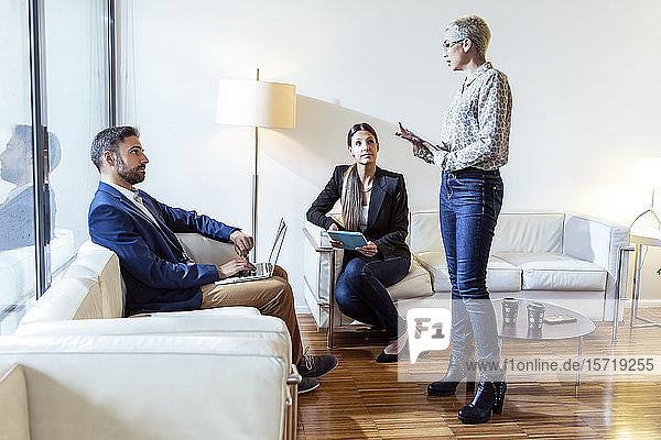 Geschäftsfrau im Gespräch mit Kollegen in der Lounge