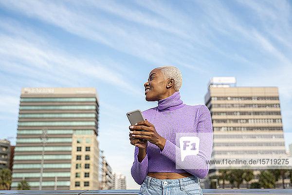 Porträt einer weißhaarigen Frau mit Smartphone in der Stadt