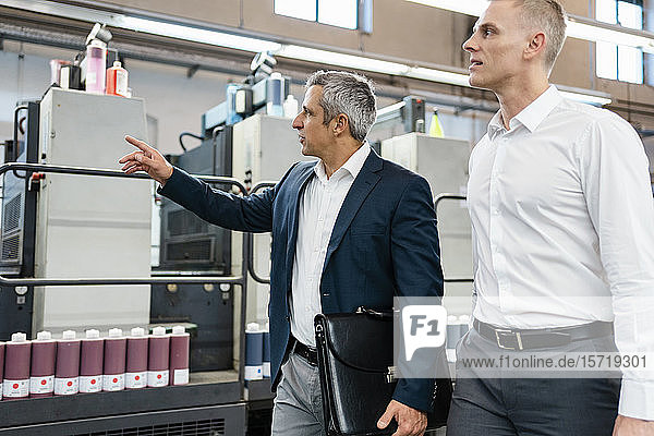 Zwei Geschäftsleute im Gespräch in einer Fabrik