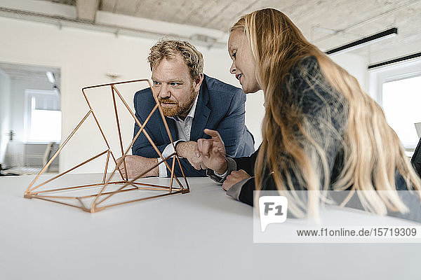 Businessman and businesswoman in office discussing object