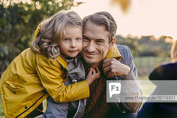 Portrait of girl hugging smiling father outdoors in autumn