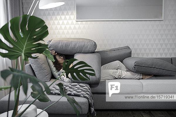 Frau entspannt sich zu Hause auf der Couch
