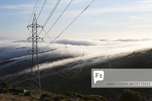 Spain  Electricity pylon against hills of Gibraltar shrouded in clouds